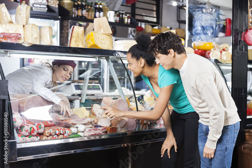 Fotografie, Obraz  Couple Choosing Product From Display Cabinet While Saleswoman As