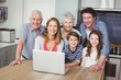 Portrait of happy family using laptop in kitchen