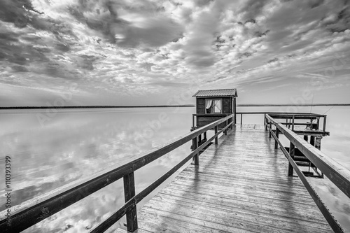 Fotografie, Obraz  Old Wooden Pier For Fishing, Small House Shed And Beautiful Lake
