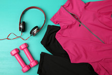 Sporting A Pink Shirt And Black Sweat Pants With Pink Dumbbells Near Headphones Premium  On A Turquoise Background