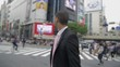 Confident young mix race business man walking Hachiko Exit Shibuya crossing Japan.
