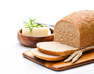 Sliced  slow-baked organic wholemeal bread with butter and rosem