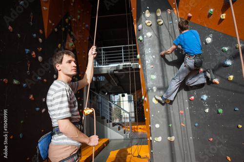 Guy holding a rope with belay device and carbine and belaying the climber on roc Wallpaper Mural