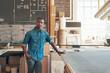 Young African designer standing confidently in his workshop studio