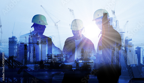 silhouette black man survey and civil engineer stand on ground working in a land building site over Blurred construction worker on construction site Canvas-taulu