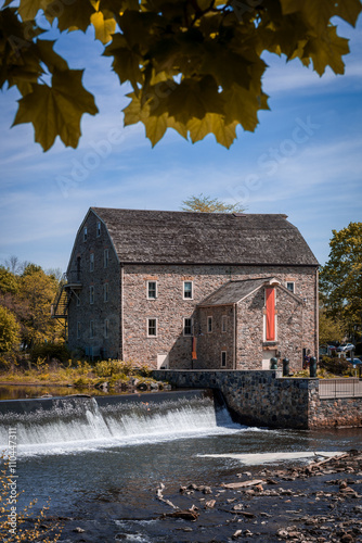 Photo  Antique gristmill along side river with dam