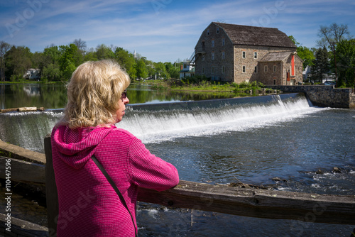 Photo  Woman looking across riverand dam to an antique gristmill
