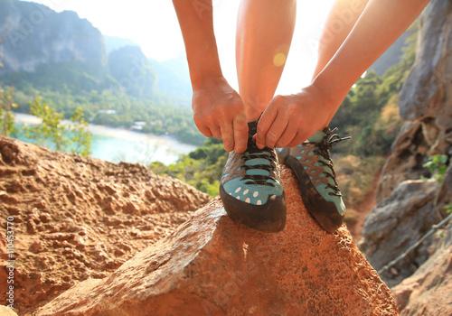 Poster de jardin Alpinisme young woman rock climber tying shoelace at mountain rock