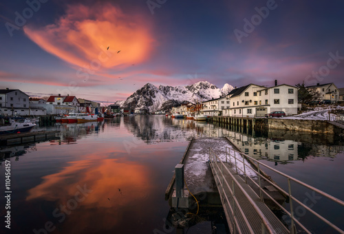 In de dag Noord Europa Colorful sunset in Henningsvaer harbor with big orange cloud and snowy mountains, Lofoten