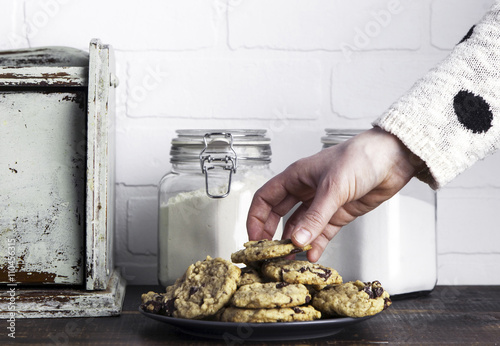 Hand taking cookie from plate Poster