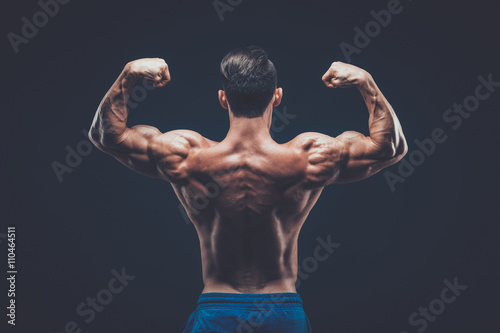 Foto Muscular man posing in dark studio on black background.