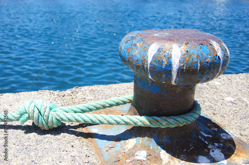 Fotografía  Old mooring bollard with  tied knot at a Harbor