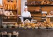 Mature bakery employee offering bread .