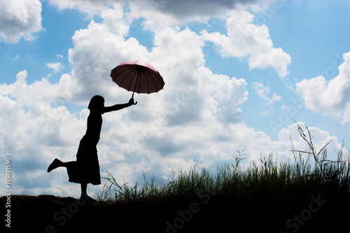 Spoed Foto op Canvas Luchtsport silhouette of woman holding umbrella sunny day