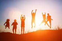 Silhouette Of Children Jump Gl...