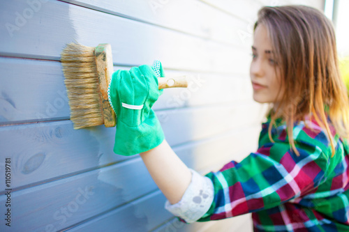 Fotografía Young woman applying protective varnish or paint on wooden house tongue and groove cladding elevation wall