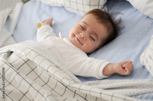 Obraz Smiling baby girl lying on a bed sleeping on blue sheets - fototapety do salonu