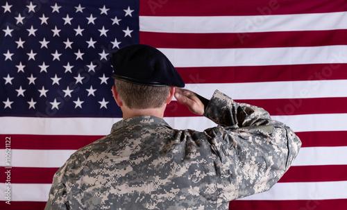 Photo  Veteran solider saluting the flag of USA flag