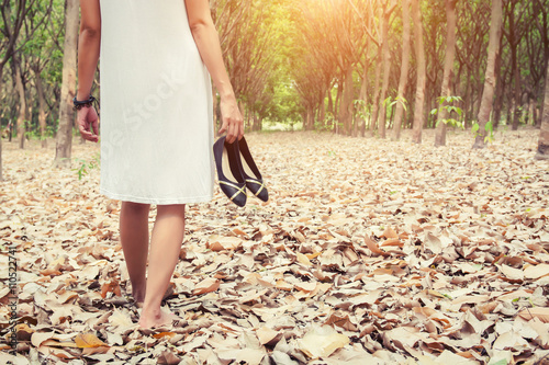 Back of young woman carrying shoes and walking in the green fore