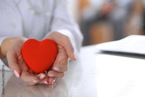Fotografia  Female doctor with stethoscope holding heart