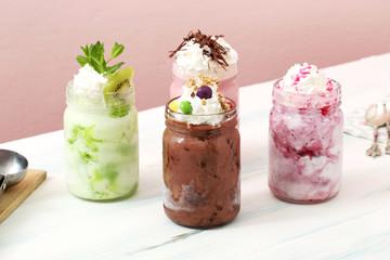 gelato con cioccolato e frutta mista in vasetti di vetro su tavolo
