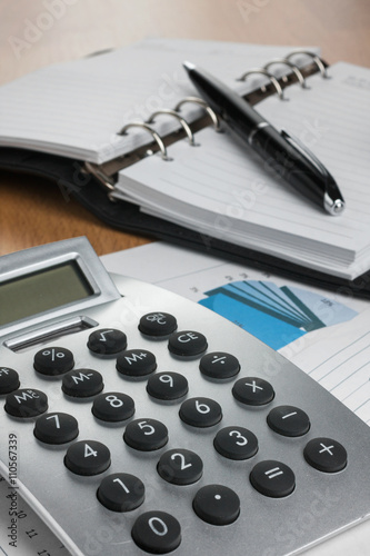 Calculator and pen on financial notebook in the diagram - 110567339