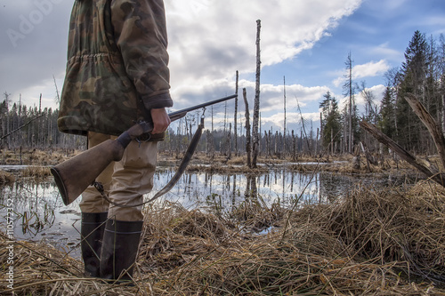 Papiers peints Chasse Hunter standing in the swamp in the forest and holding in his hand an old hunting rifle