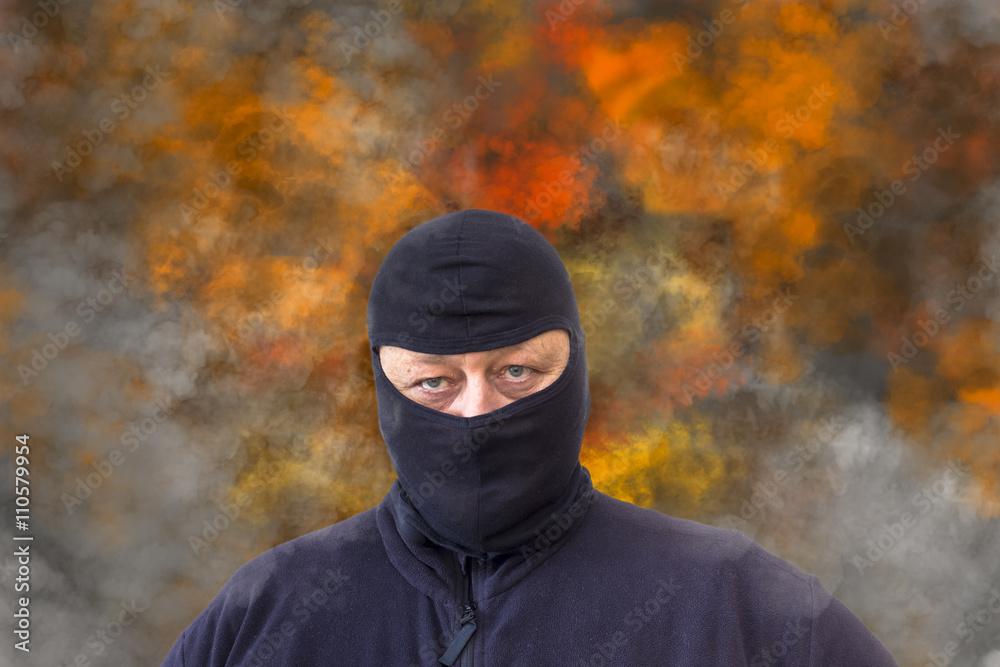 Fototapeta Mann mit Sturmhaube vor einem Hintergrund aus Rauch und Flammen