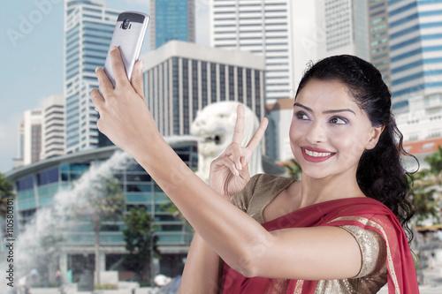 Photo  Indian woman taking selfie at Singapore city