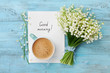 Leinwandbild Motiv Coffee mug with bouquet of flowers lily of the valley and notes good morning on turquoise rustic table from above, beautiful breakfast, vintage card, top view, flat lay