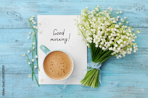 Fotografia Coffee mug with bouquet of flowers lily of the valley and notes good morning on