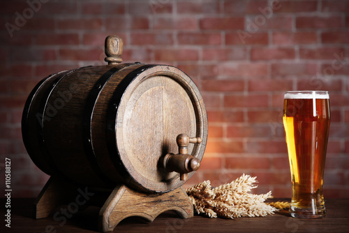 Papiers peints Affiche vintage Glass of light beer with wooden barrel and barley ears on brick wall background. Retro stylization