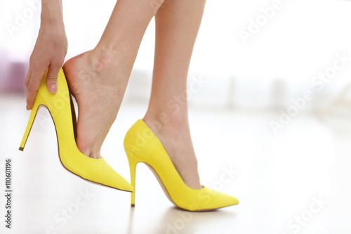 Cuadros en Lienzo Woman taking off yellow high heels shoes.