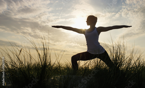 Fotografie, Obraz  Silhouette of a young woman in a yoga warrior pose on a beach hilltop