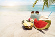 Summer vacation concept with straw hat, sunglasses and fruit on sandy tropical beach