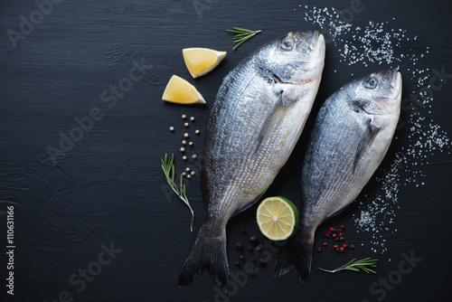 Fotografie, Obraz  Sea breams with seasonings on a black wooden surface, above view