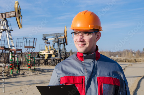 Staande foto Industrial geb. Worker wearing orange helmet in the oilfield. Pump jack background. Oil and gas concept.