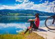 Leinwandbild Motiv woman with e-bike enjoying view over lake-lake and bike 03