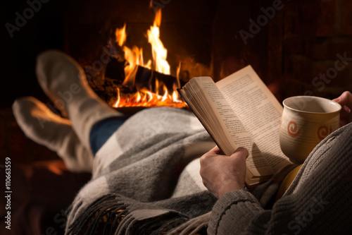 Obraz Woman reads book near fireplace - fototapety do salonu