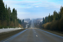 A Hilly Winter Road With A Forest Around And The Road Going Up And Down