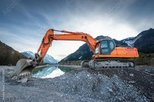 Fotografie, Obraz  side view of orange shovel digger on gravel at lake and blue sky
