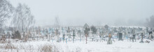 Panorama Of Foggy Gloomy Snowy Cemetery  With Crosses And Headstones