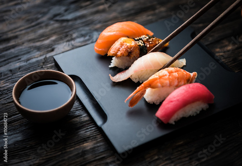 close up of sashimi sushi set with chopsticks and soy on black background
