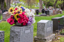 Flowers On A Tombstone In A Ce...