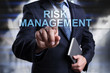Businessman is pressing button on virtual screen and selecting Risk MAnagement.