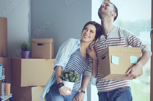 Fotografiet  Happy young couple unpacking or packing boxes and moving into a new home