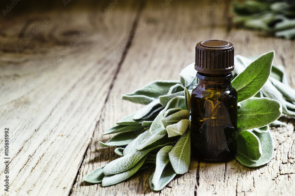 Fototapety, obrazy: Sage oil in brown bottle on the vintage wooden table, selective