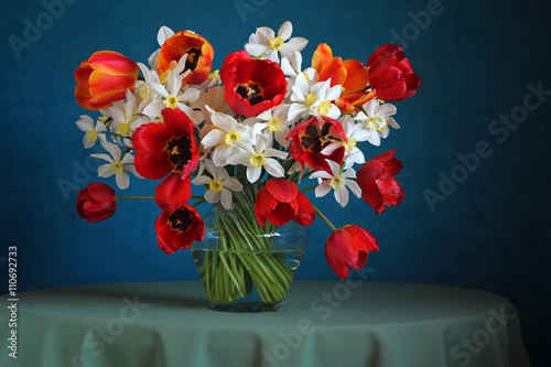 Still life with a bouquet of daffodils and tulips on a blue back - 110692733