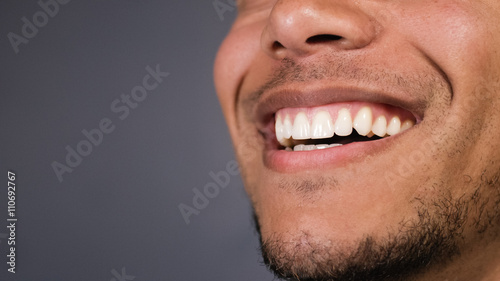 Leinwand Poster  Healthy teeth of a male as he smiles at something, space for text