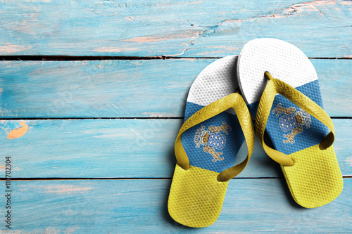 Tuinposter Canarische Eilanden Thongs with flag of Canary Islands, on blue wooden boards